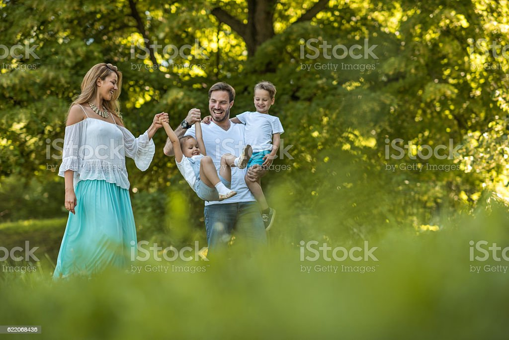 Playful parents having fun with their small kids in nature. stock photo