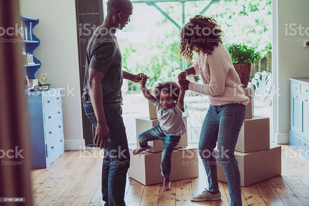 Playful parents holding son's hands in new house stock photo