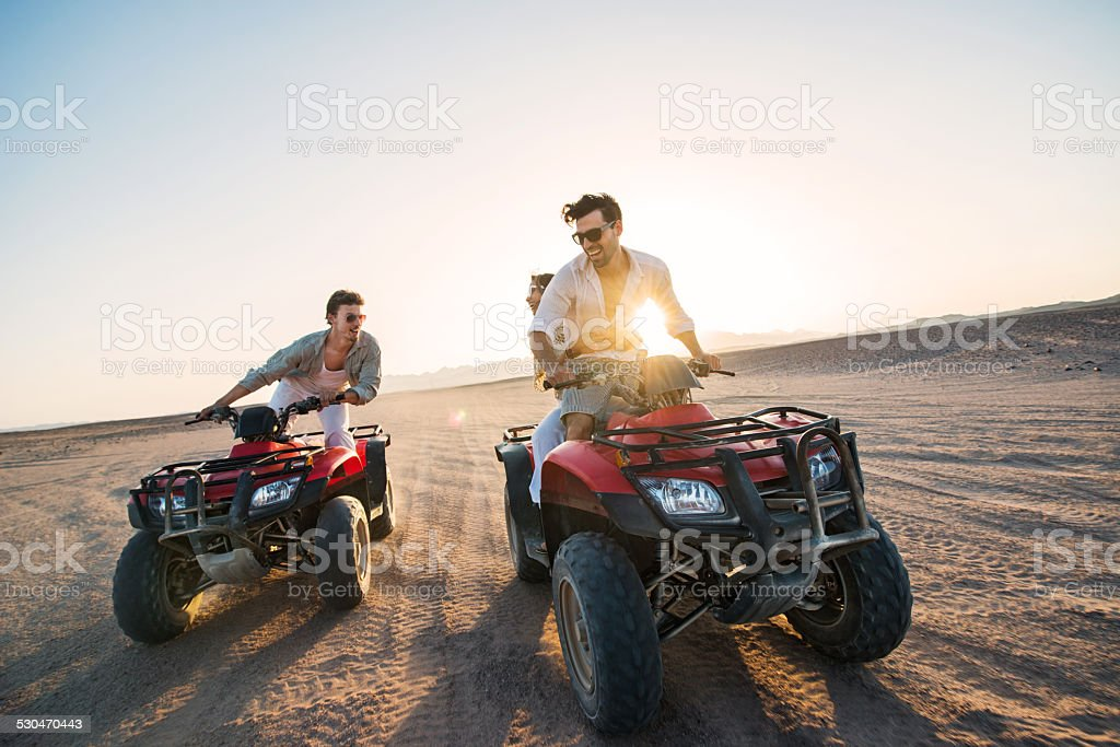 Playful people on quad bikes in the desert. stock photo