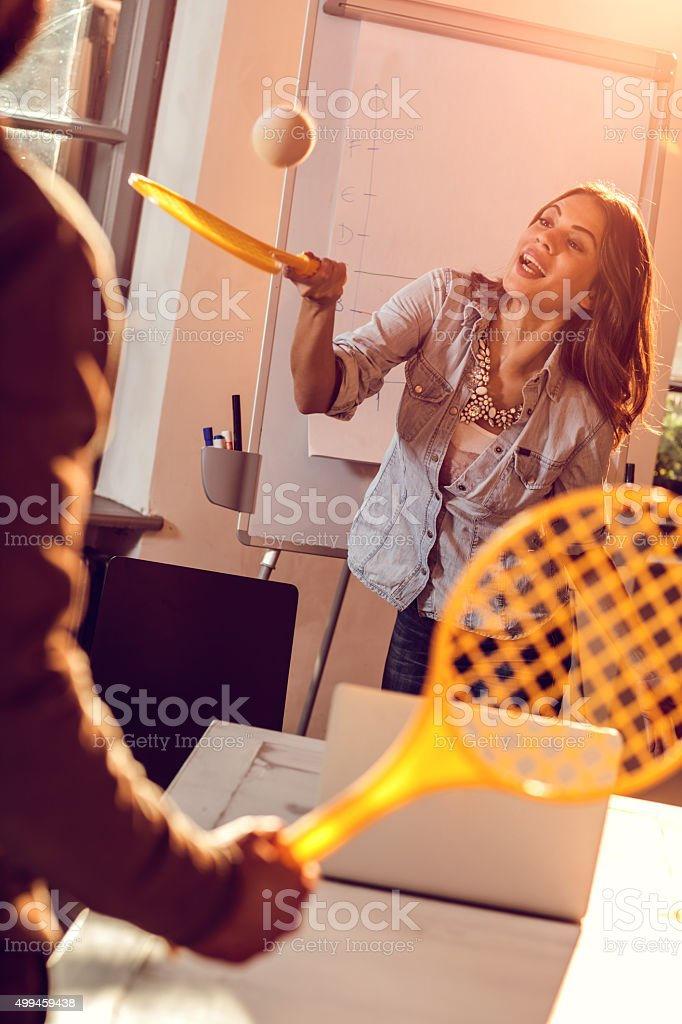 Playful people playing tennis with plastic rackets at office. stock photo