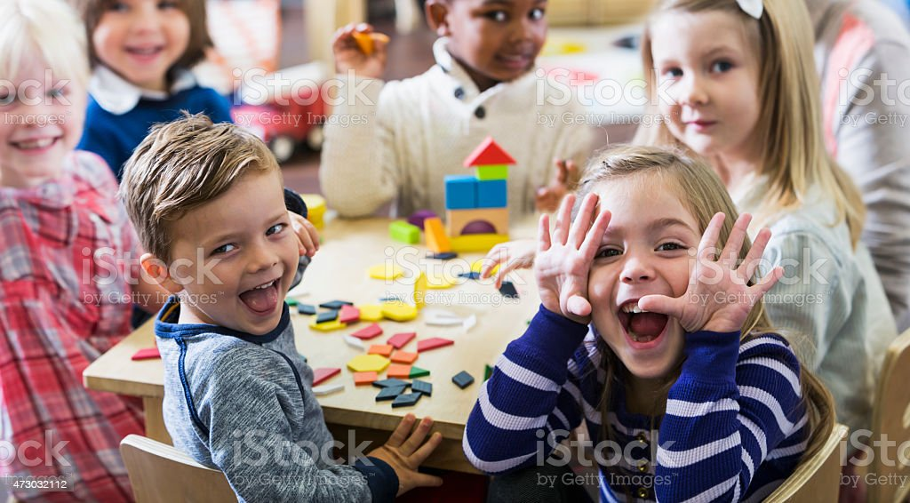 Playful preschoolers having fun making faces stock photo