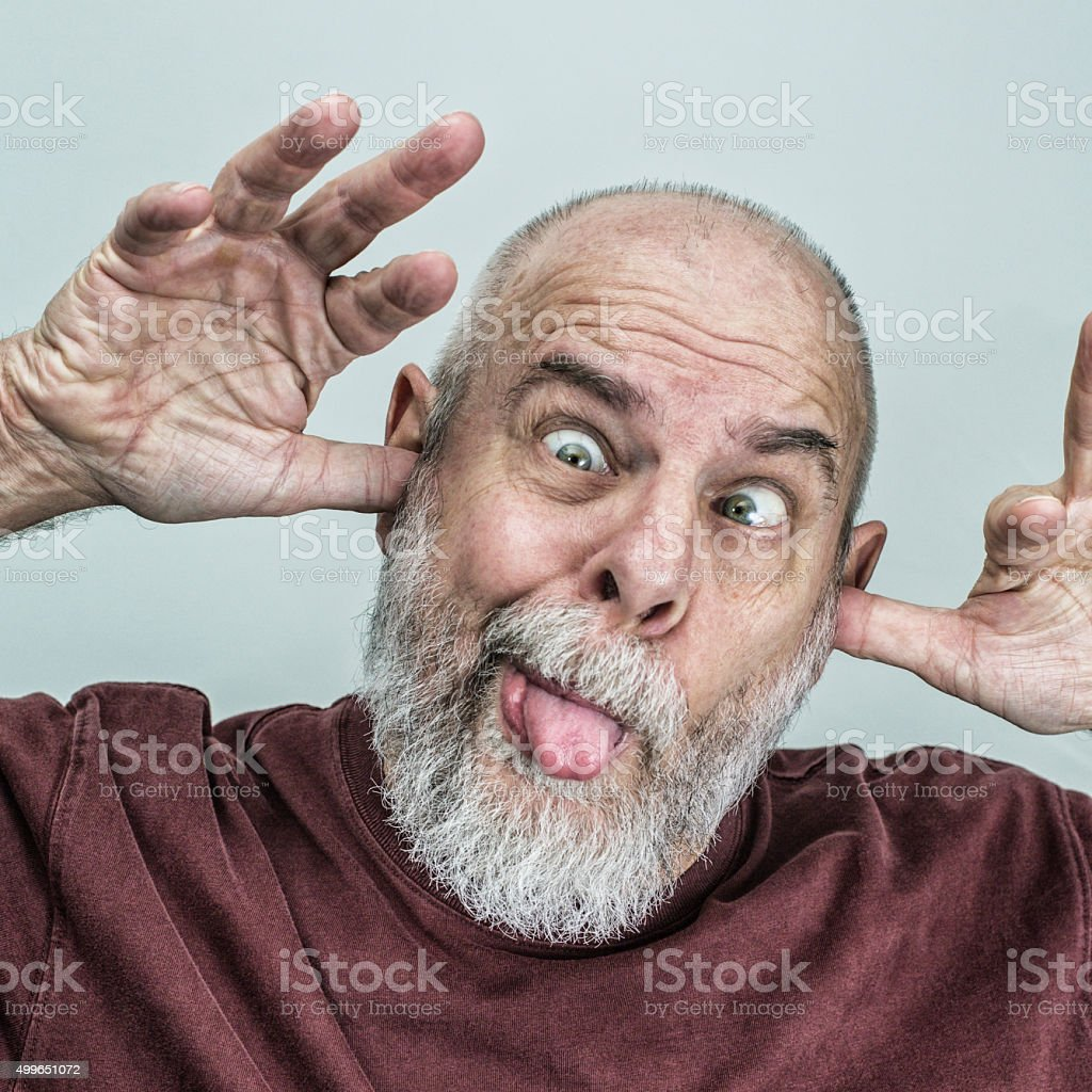 Playful Senior Adult Man Sticking Tongue Out Making Funny Face stock photo