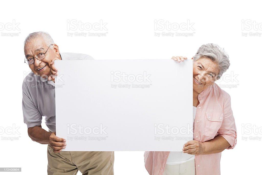 Playful senior couple holding a sign stock photo