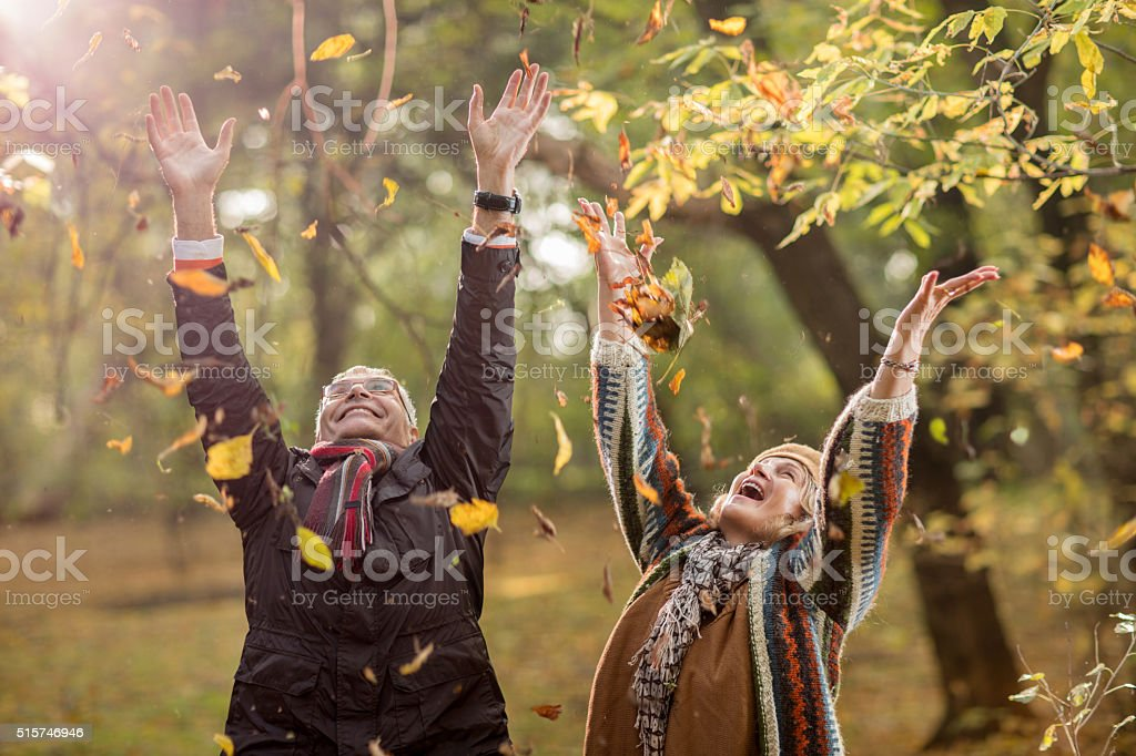 Playful senior couple throwing autumn leaves high up. stock photo