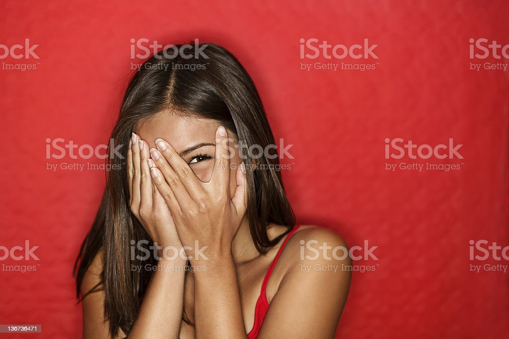 Playful shy woman hiding face laughing stock photo