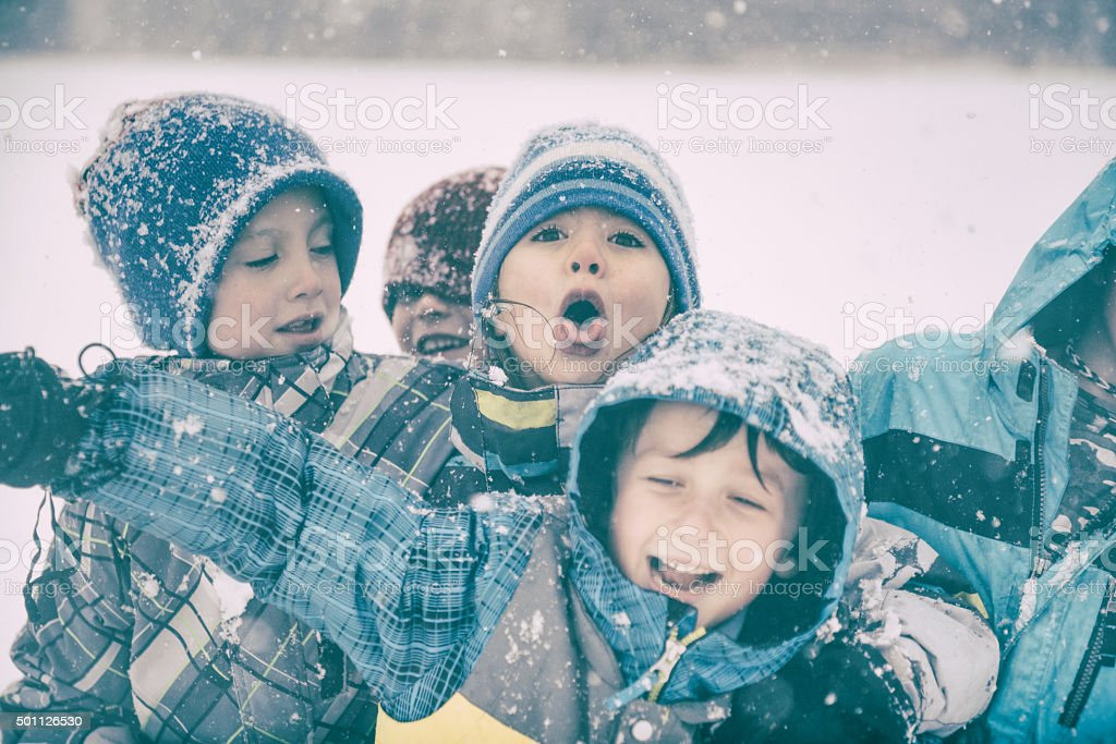 Playful silly children enjoy the snow on a stormy day stock photo