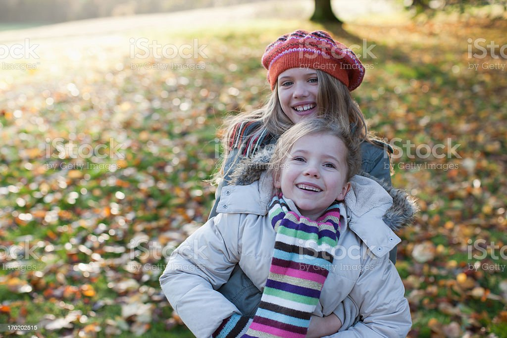 Playful sisters smiling outdoors in autumn stock photo