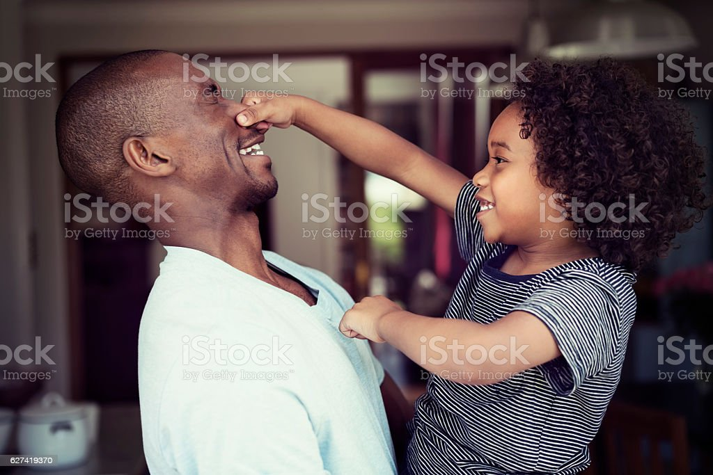 Playful son pulling father's nose at home stock photo