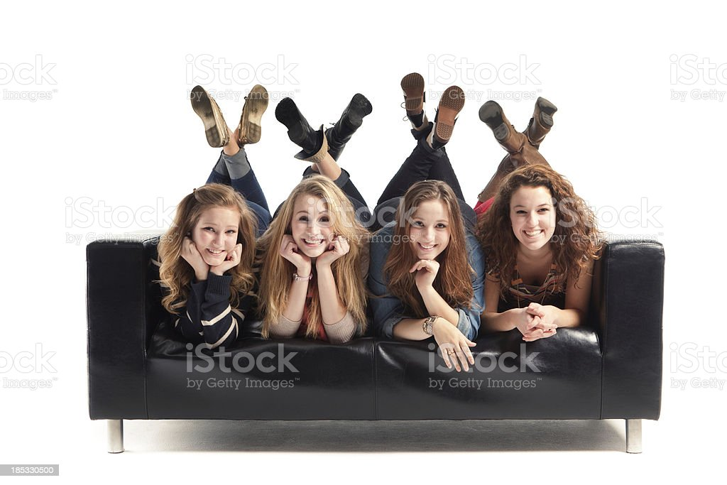 Playful Teen Girls in Black Sofa on White Background royalty-free stock photo