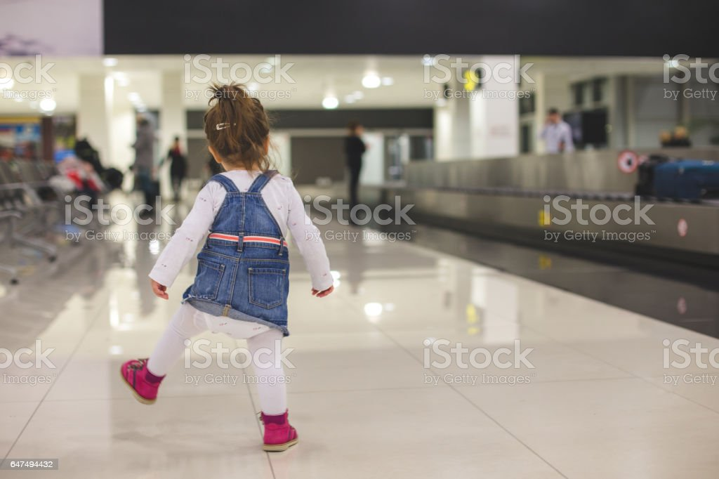 Playful toddler at arrival area at airport stock photo