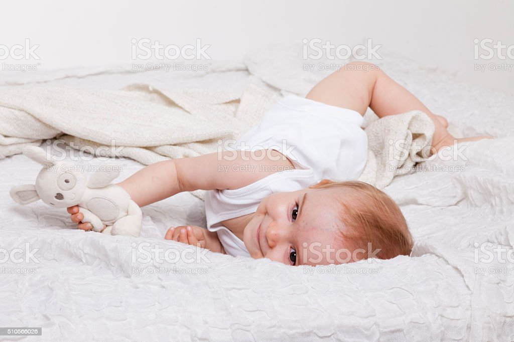 playful toddler girl in bed stock photo