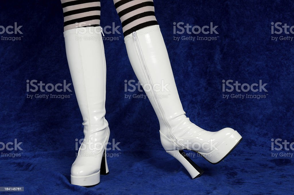 Playful white boots on blue. stock photo
