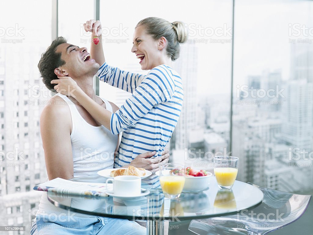 Playful woman feeding strawberry to husband at breakfast stock photo
