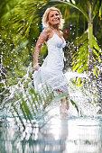 Playful woman having fun in water at tropical resort.