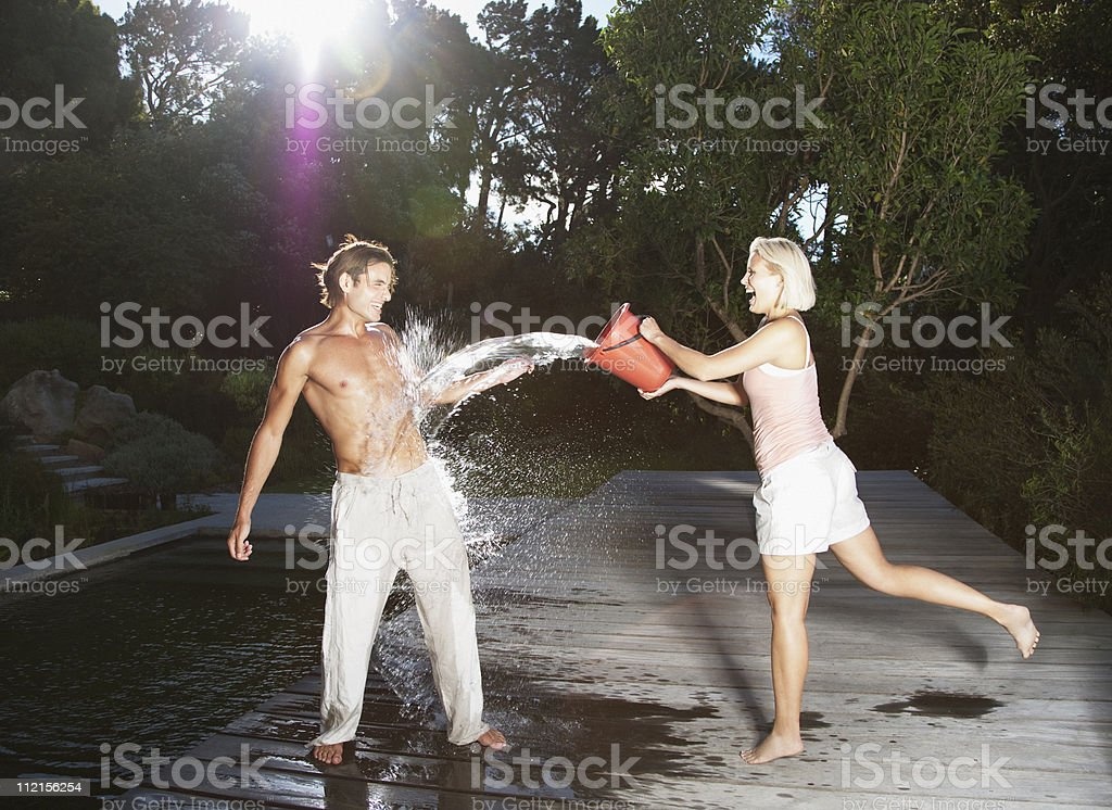 Playful woman throwing bucket of water on boyfriend royalty-free stock photo