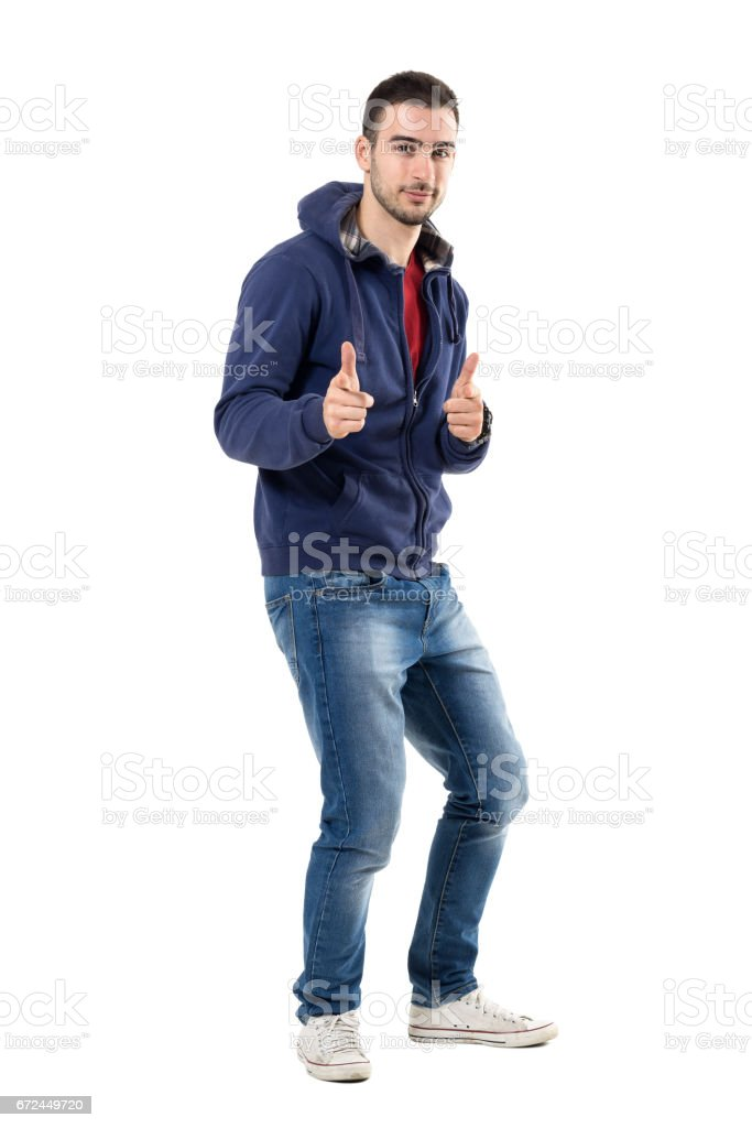 Playful young casual man in sweatshirt with finger gun gesture aiming at camera stock photo