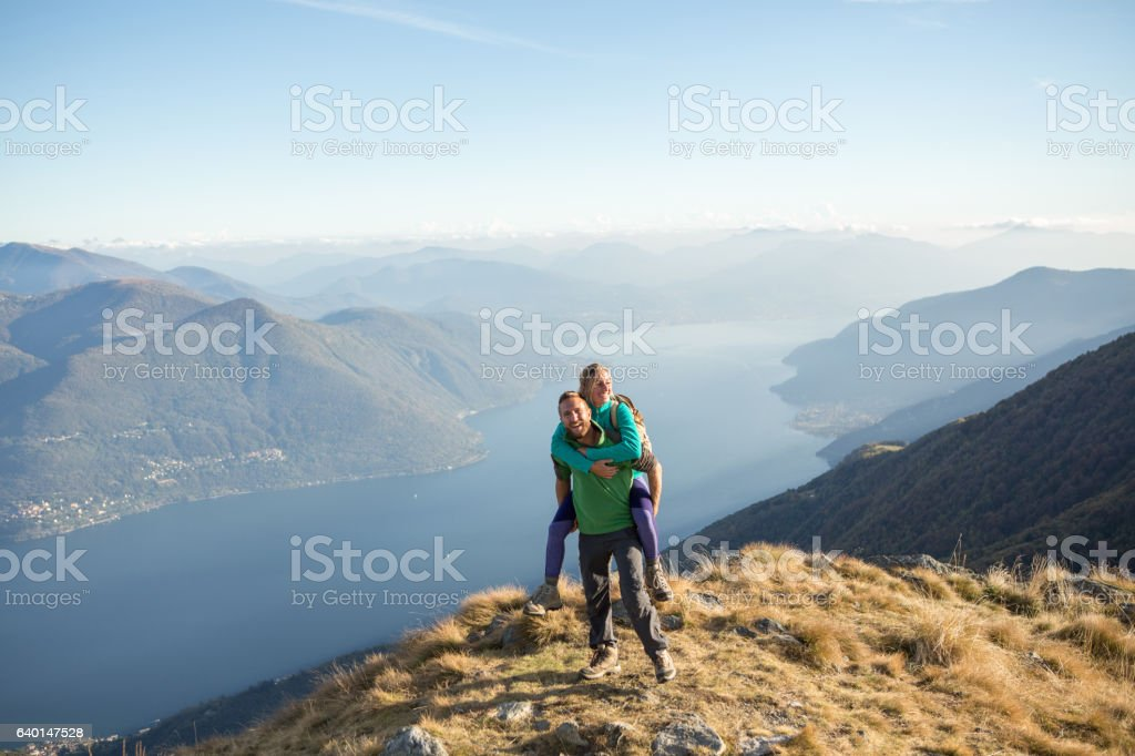 Playful young couple on mountain top stock photo