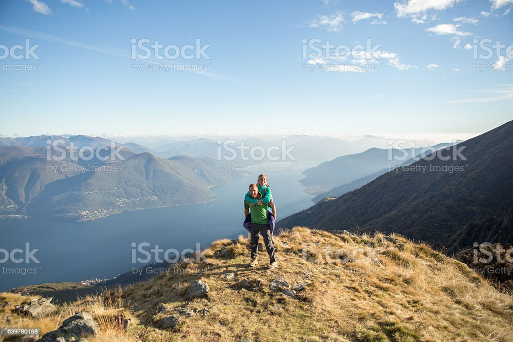 Playful young couple on mountain top, piggyback stock photo