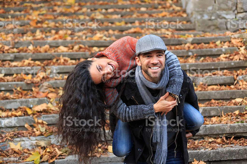 Playful young couple standing on stairs and having fun stock photo
