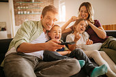 Playful young family watching television