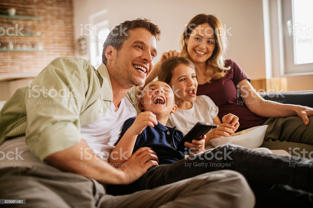 Playful young family watching television stock photo