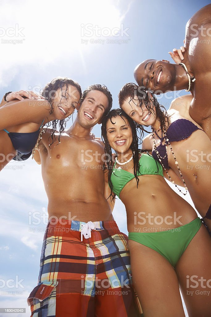 Playful young friends enjoying together on beach against sky royalty-free stock photo