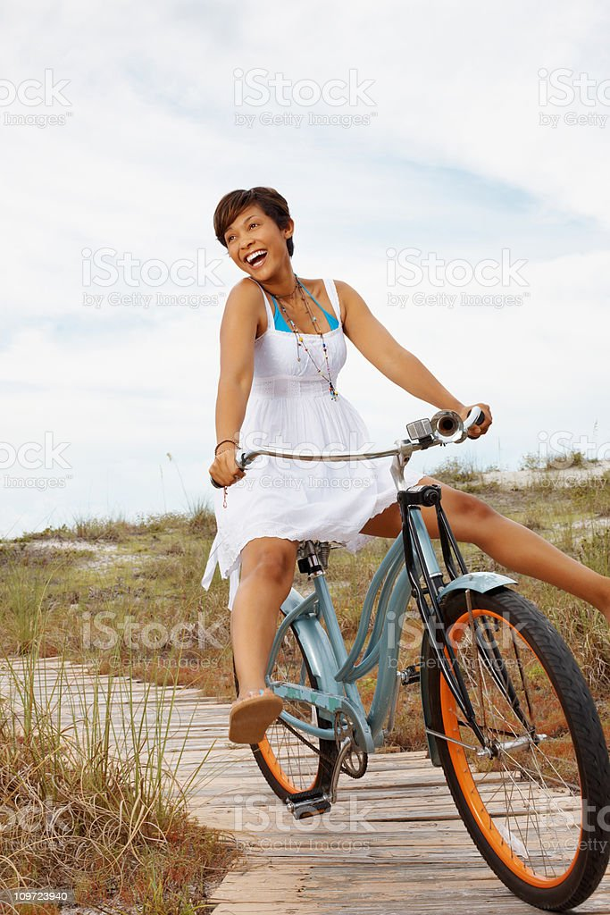 Playful, young woman in sundress riding bicycle on the beach royalty-free stock photo