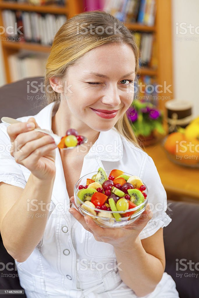 Playful young woman offering teaspoon full of sliced ​​fruits, smiling royalty-free stock photo