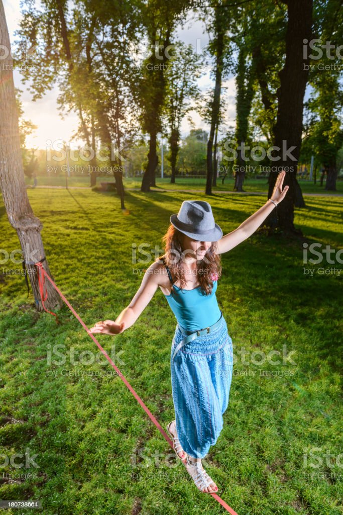 Playful  young woman on slackline stock photo