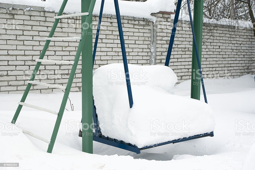 playground swing cover in fluffy white snow stock photo
