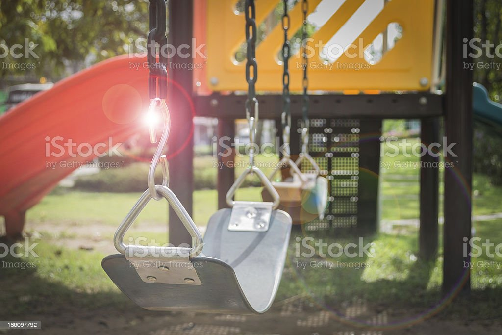 Playground swing set with lens flare (selective focus) royalty-free stock photo