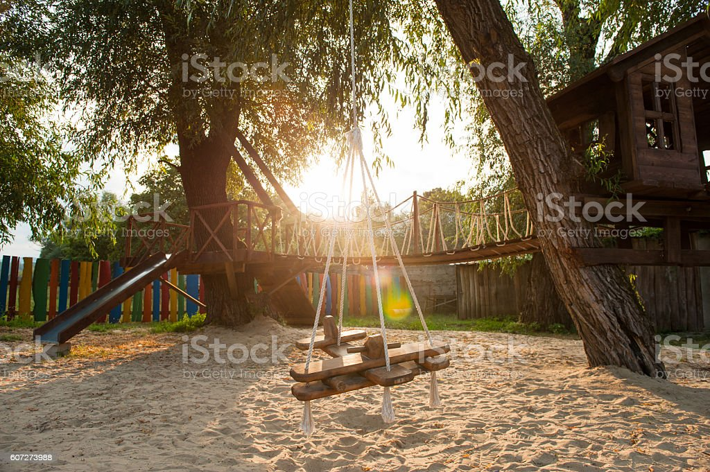 playground with a hanging swing at sunset stock photo
