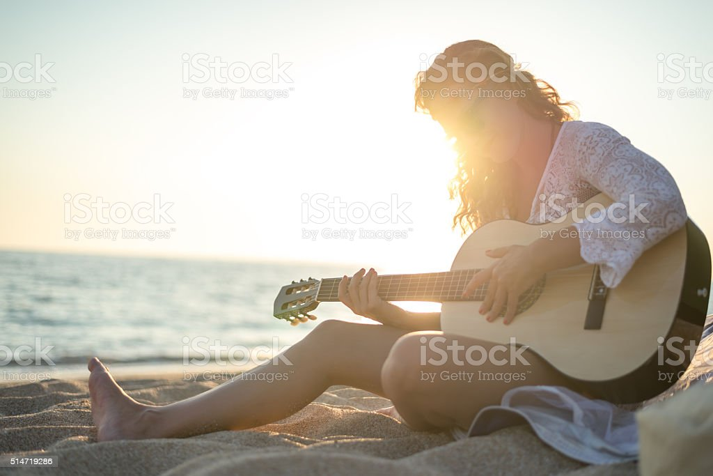 Playing a guitar at the beach stock photo