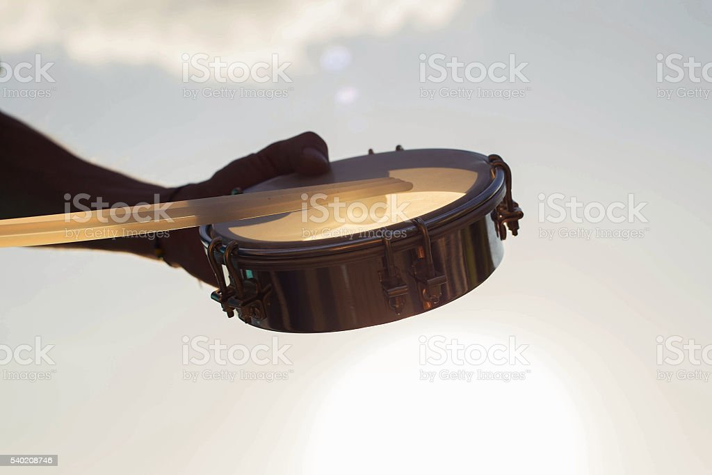 Playing a musical instrument tambourine on background sky at sunset stock photo