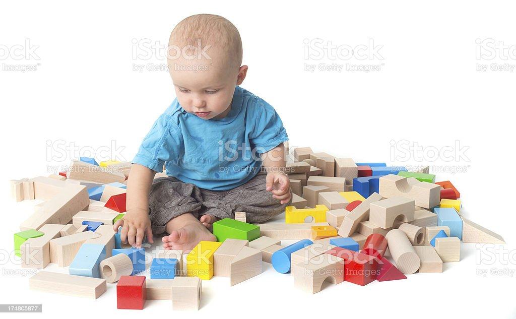 playing Baby with log of woods in studio seeking stock photo