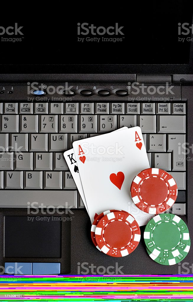 Playing cards and poker chips on top of a computer keyboard  stock photo
