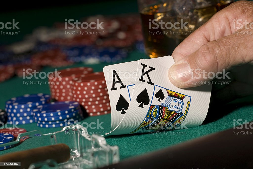 Playing cards being looked at with poker chips in background royalty-free stock photo