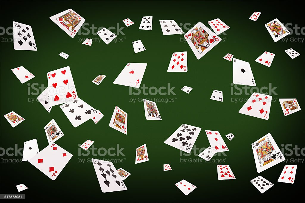 Playing cards flying at the poker table stock photo
