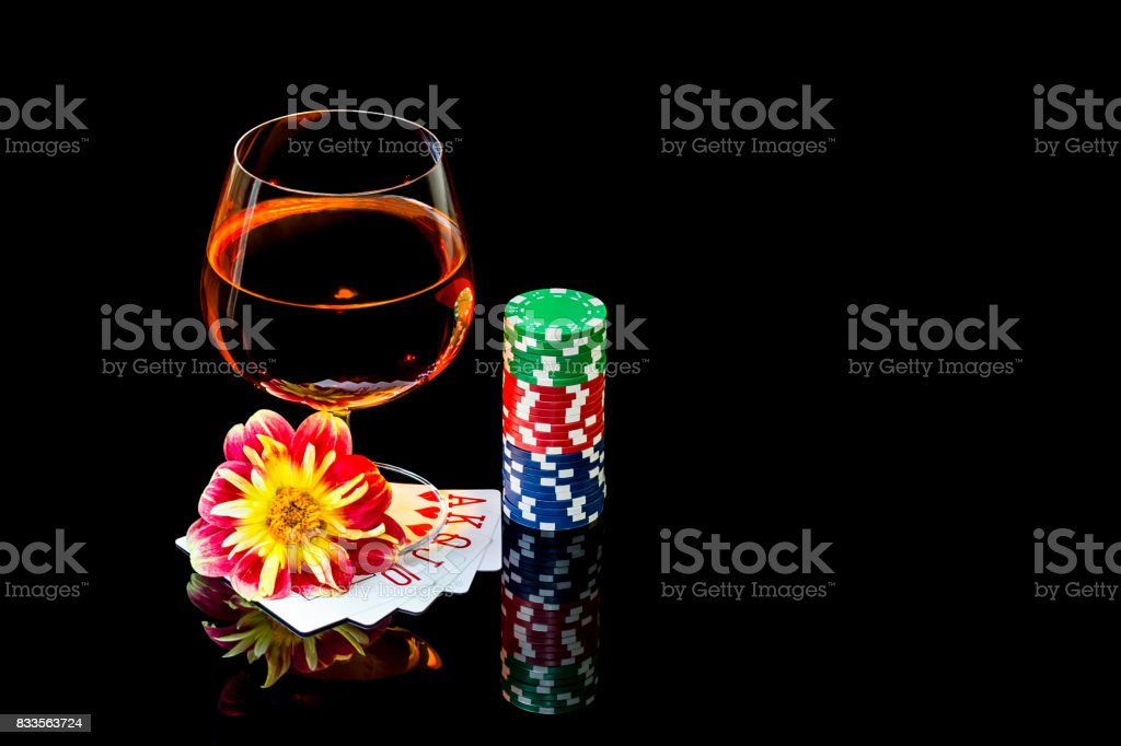 Playing cards with colorful chips to play poker and snifter of brandy stock photo