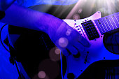 playing electric guitar in blue