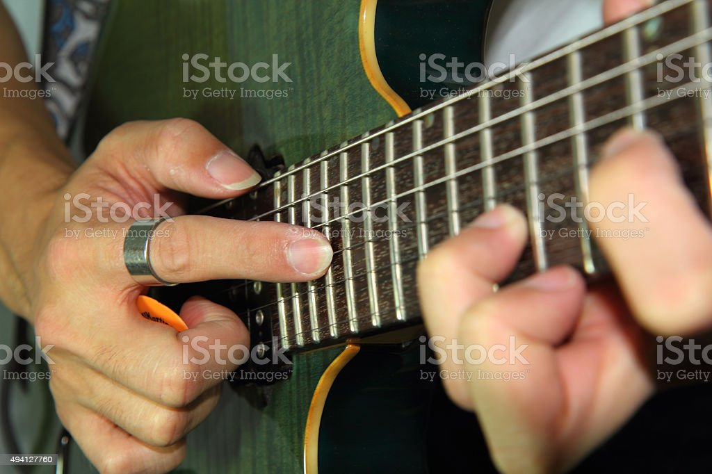 playing electric guitar with taping technic stock photo