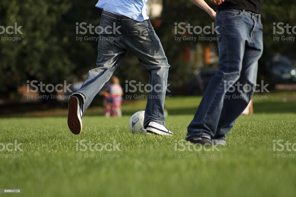 Playing football in the park stock photo