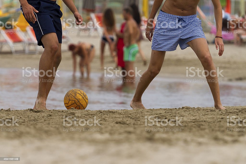 playing football on the beach stock photo