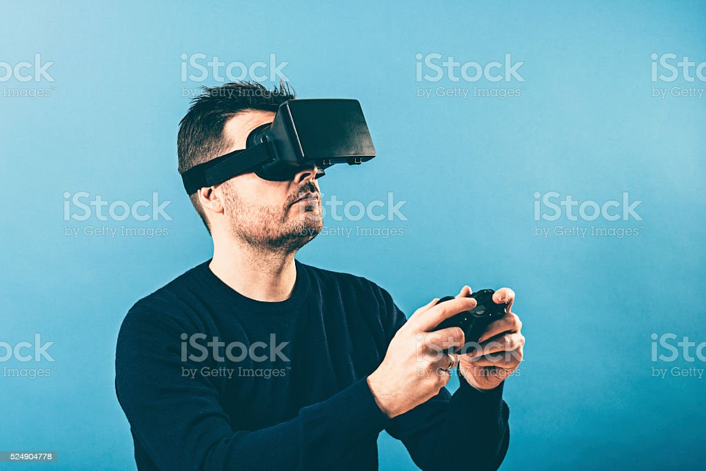 Playing game with controller while wearing virtual reality glasses stock photo