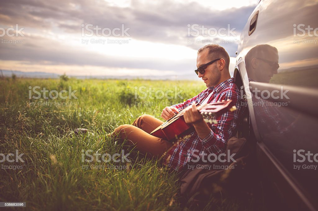 Playing guitar in nature stock photo