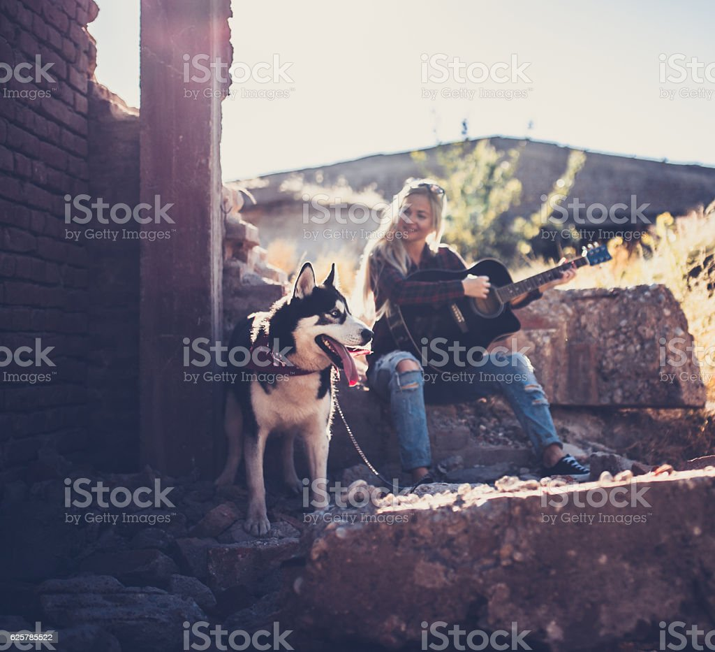 Playing guitar next to huskey dog stock photo