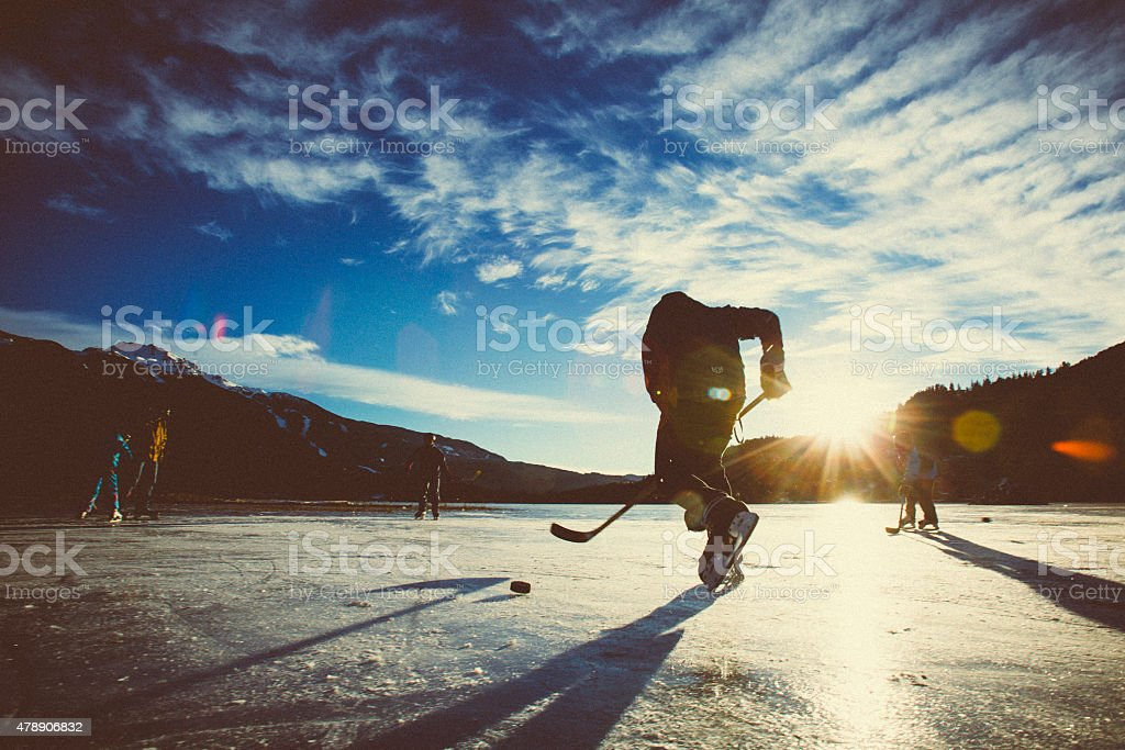 Playing ice hockey on frozen lake in sunset. stock photo
