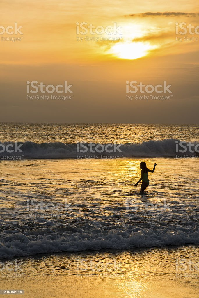Playing in the waves at sunset. stock photo
