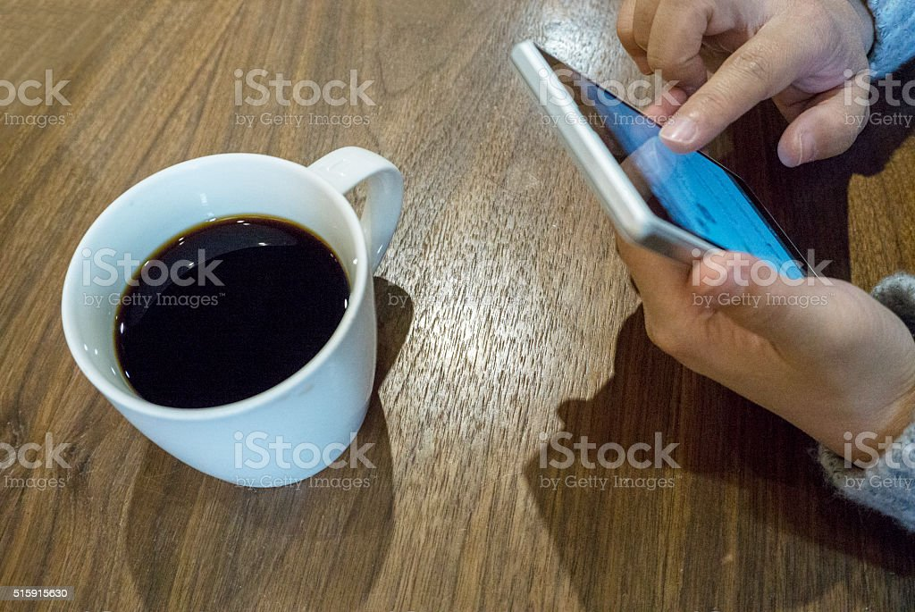 playing mobile phone in cafe stock photo