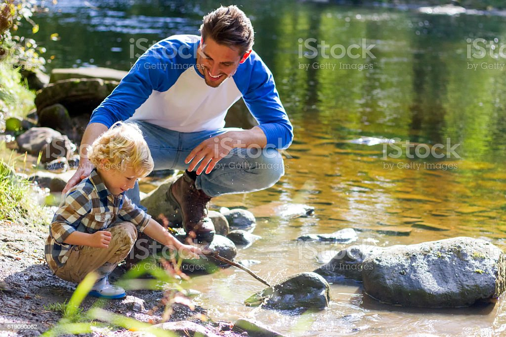 Playing next to the lake with dad stock photo